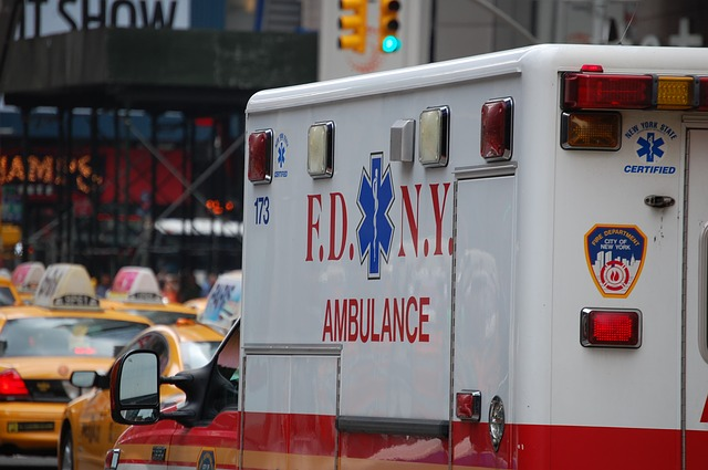 a red and white new york city ambulance on a busy street